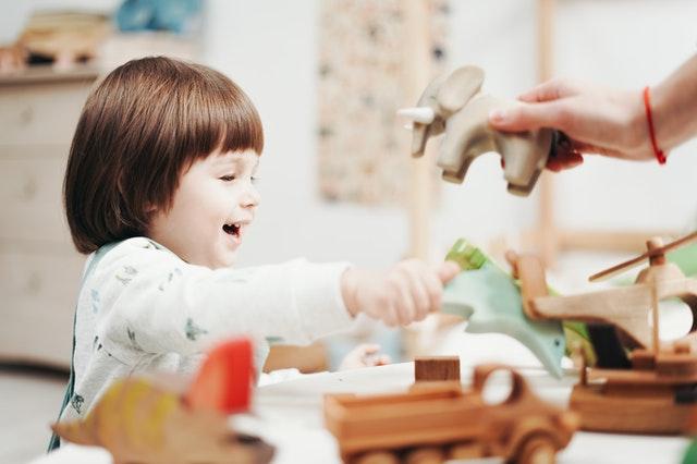 gyerek fa játékkal játszik